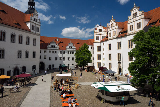 The interior courtyard at Hartenfels Castle in Torgau with a holiday weekend event taking place for local residents and visitors (photo © hidden europe).